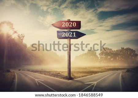 Surreal scene with a split road and signpost arrows showing two different courses, left and right, past and future, old 2020 and the new 2021 year direction to choose. Life decision, choice concept. Stock photo ©