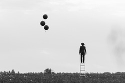 surreal silhouette of a man in a suit standing on the stairs in a field with balloons. Concept of freedom