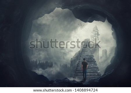 Surreal view as a man escape from a dark cave climbing a mystic stairway crossing the misty abyss going up to unknown paradise. Opportunity staircase, exit way to success, freedom concept. ストックフォト ©
