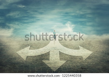 Surreal view as a man walking in front of a crossroad where road is splitted in three different ways as arrows. Choosing the correct pathway between left, right and front. Difficult decision concept.