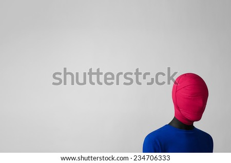 Stock Photo Surrealism Theme: man in a blue jacket with a pink cloth tied around his head is in the corner on a gray background