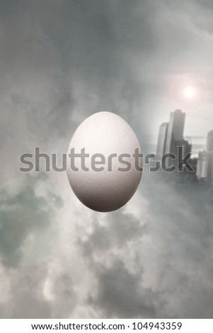 Surrealist float of an egg between cloudy dramatic sky with a modern city on the background