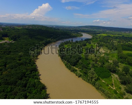 Surrounded by deep green woods,  dirty after big flood The Prut river near city of Chernivtsi, Western Ukraine, aerial summer view. Catastrophic deluge, overflow, freshet. Beauty of Mother-Earth.  Foto stock ©