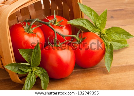 Surrounded by sweet basil, four red juicy vine ripened tomatoes fall out of a woven basket. A wooden cutting board provides the final resting place for the tomatoes before they are sliced open.