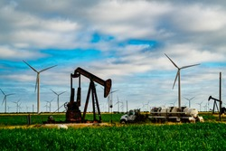 Surrounded by Wind Turbines and Oil Pump in West Texas display the Old and the New of Energy consumption , Climate Change , and the fight for Renewable Energy. Old oil tanker sits in green grass field