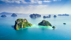 Surrounding Islands of Koh Yao Noi, Phuket, Thailand green lush tropical island in a blue and turquoise sea with islands in the background and clouds with sun beams shining through, drone aerial photo