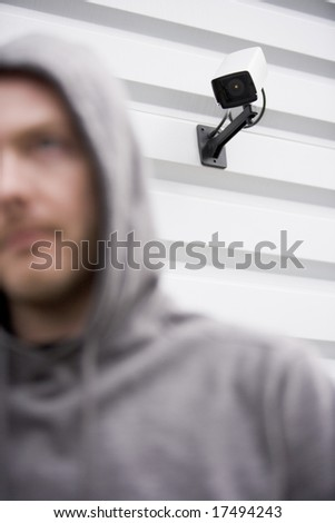 Surveillance Camera And Young Man In Hooded Sweatshirt - stock photo