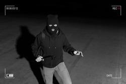 Surveillance camera caught burglar in ski mask holding crowbar while making eye contact in dark parking lot