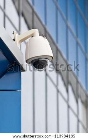 Surveillance camera on a background of blue glass wall