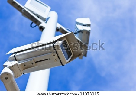 Surveillance camera on a pole, low angle view, blue sky.