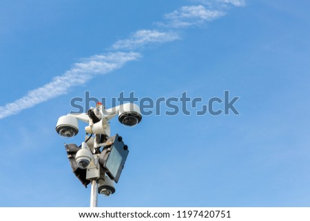Surveillance cameras, floodlights and speaker horn on top of the pole on blue sky background. #1197420751