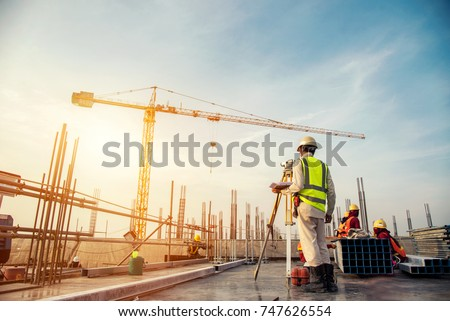 Surveyor builder Engineer with theodolite transit equipment at construction site outdoors during surveying work #747626554