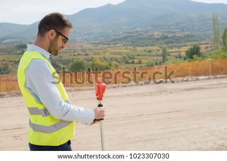 Surveyor engineer is measuring level on construction site. Surveyors ensure precise measurements before undertaking large construction projects.