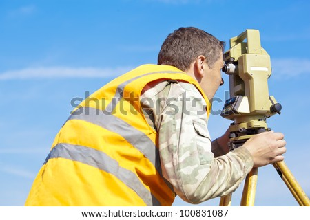Surveyor engineer making measuring with optical equipment theodolite at blue sky background