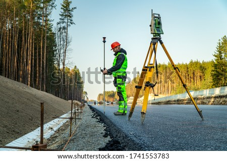 Surveyor engineer with equipment (theodolite or total positioning station) on the construction site of the road or building with construction machinery background Stockfoto ©
