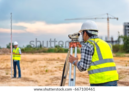 Surveyor Engineering. Surveyor's telescope at construction site. Surveying for making contour plans are a graphical representation of the lay of the land before startup construction work #667100461