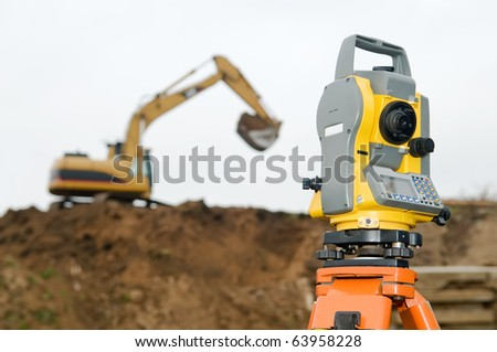Surveyor equipment theodolite on tripod at building area in front of working construction machinery loader