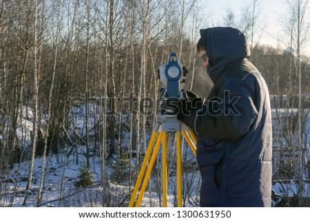 Surveyor in the winter forest conducts cadastral work