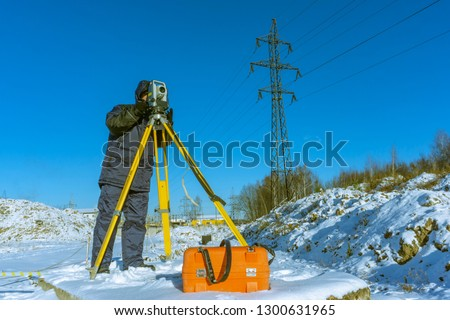 Surveyor in winter in overalls conducts a topographical survey for the cadastre