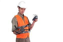 Surveyor. Man with a quadcopter in his hands on a white background. Geodetic quadcopter in hands of builder. Use of a drone for geodetic work. Topographic survey from a quadcopter. Surveyor service