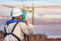 Surveyor on a construction site. A man takes measurements on a construction site. Geodesy and cartography. Measuring equipment. Builder, theodolite, and houses under construction.