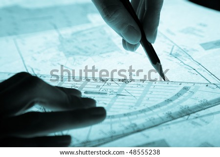 surveyor's plan and hands with a pencil, monochromatic blue - stock photo
