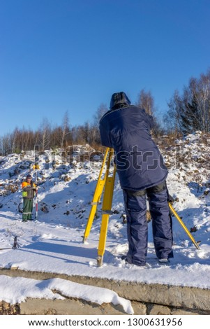 Surveyor with an assistant do a geodetic survey at a construction site