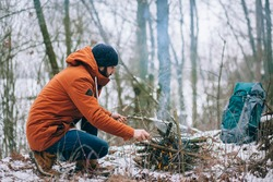 survival man is making camp fire in the winter woods