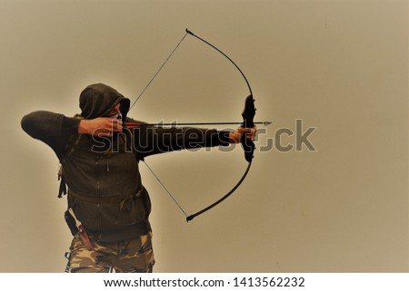 Survivalist shooting with bow and arrow #1413562232