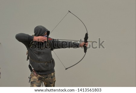 survivalsit shooting with bow and arrow #1413561803