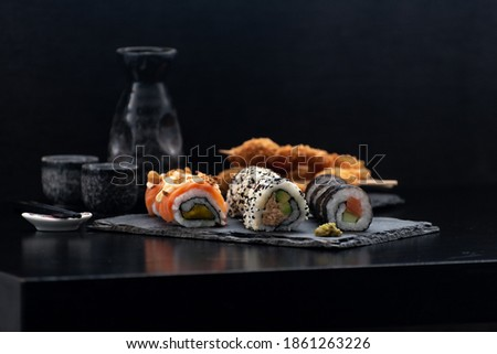 Sushi and fried garlic shrimps, prawn on a stone plate with black background