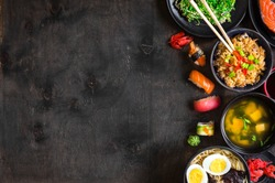 Sushi and japanese food on dark background. Sushi rolls, hiyashi wakame, miso soup, ramen, fried rice with vegetables, nigiri, soy sauce, chopsticks. Asian/Japanese food frame. Overhead