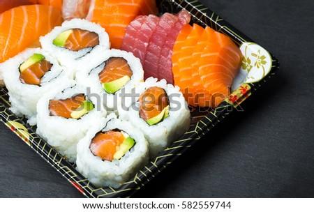 Sushi and Sashimi rolls on a black stone slatter. Fresh made Sushi set with salmon, prawns, wasabi and ginger. Traditional Japanese cuisine.