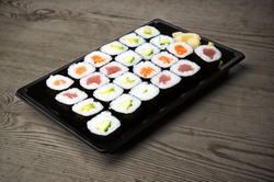 Sushi and Sashimi rolls on a wooden table. Fresh made Sushi set with salmon, prawns, wasabi and ginger. Traditional Japanese cuisine.