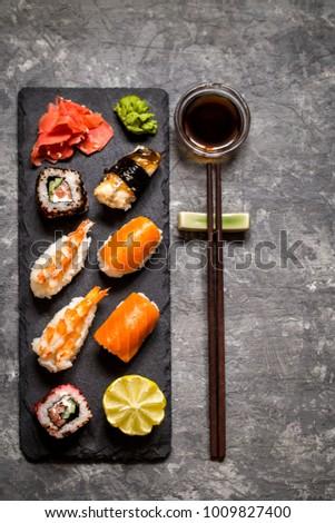 sushi and sushi rolls, sushi nigiri on stone plate on dark background, mustard wasabi, and ginger