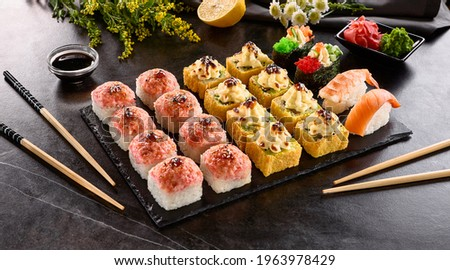 Sushi bar set - International maki sushi roll on black slate platter. Served with wooden chopstick, wasabi and pickled ginger. Japanese set with maki sushi roll and nigiri sushi on dark stone table