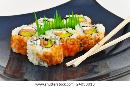 Sushi California Philly rolls appetizer with rice, avocado, and salmon on square blue plate w/ chopsticks