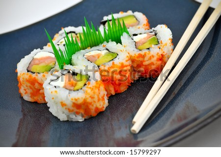 Sushi California rolls with rice, avocado, and salmon on a blue plate with chopsticks.