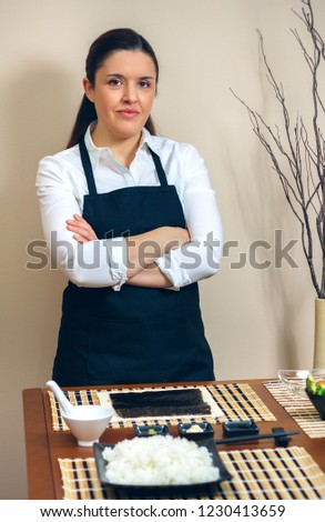 Sushi chef posing in front of table with cooking preparations