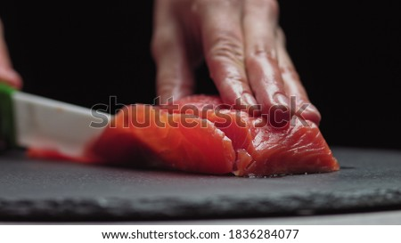 Sushi Chef Slices fresh Salmon on the sushi bar. Chef cutting salmon fillet at professional kitchen. Closeup chef hands slicing fresh fish slice in slow motion. Professional man cutting red fish