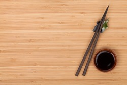 Sushi chopsticks and soy sauce bowl over bamboo table with copy space