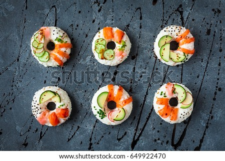 Sushi donuts set on black background. Sushi trend. Creative food. Flat lay, top view