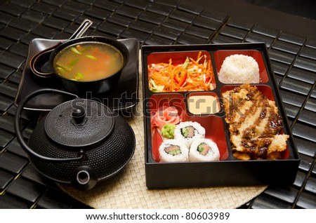 Sushi lunch with soup salad tea and sauce - stock photo