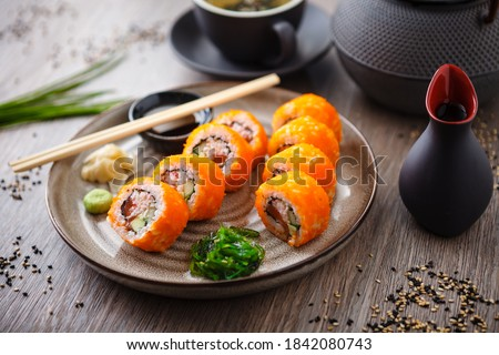 Sushi maki rolls California Futomaki with salmon, avocado, cucumber, crab and flying fish roe on a plate with chopsticks, soy sauce, wasabi and ginger. Japanese traditional seafood served restaurant.