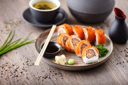 Sushi maki rolls with spicy crab, salmon, cucumber on a plate with chopsticks, soy sauce, wasabi and ginger. Japanese traditional seafood served for lunch in modern gourmet restaurant.