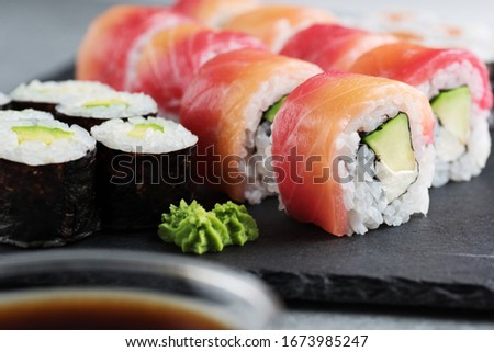 Sushi maki with avocado and sushi philadelphia on a background of slate board.