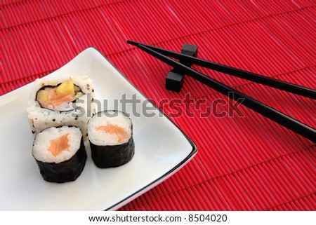 Sushi on a plate with chopsticks on a red bamboo placemat