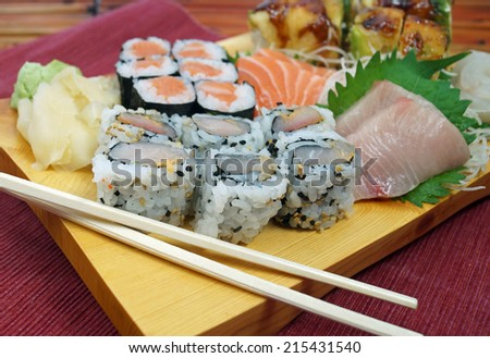Sushi Plate. Japanese sushi plate with salmon and yellow tail snapper sashimi, salmon roll, scallop roll and chopsticks on a stylish wood serving board.