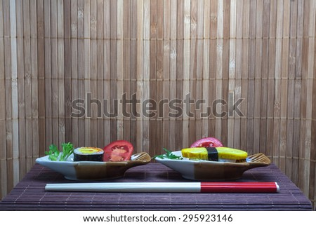 Sushi put into Small plates with bamboo mat background. Focus on Sushi. Design with space for adding text or montage of your product. Sushi  is a Japanese food consisting of cooked rice.