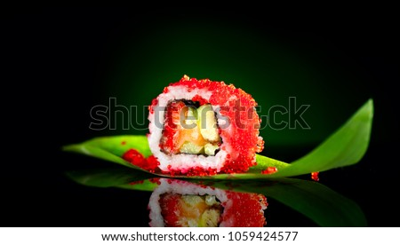 Sushi roll isolated on black background. Sushi japanese food in restaurant. Piece of California Sushi roll set with salmon, vegetables, flying fish roe and caviar closeup. Japan restaurant menu.